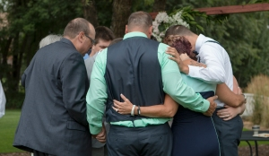 Family prayer around the bride and groom.